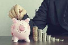 la mano delle donne di affari ha messo i soldi sul rosa del porcellino salvadanaio Immagine Stock