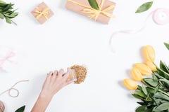 La mano delle donne ha decorato la tavola con i fiori e le scatole con il GIF Immagine Stock