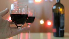 La mano delle donne prende un vetro con vino rosso Tabella con due vetri e bottiglie di vino stock footage