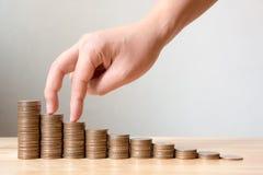 La mano delle monete maschii o femminili di punto del dito impila crescita crescente sa Fotografie Stock