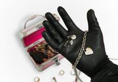 La mano delle tenute del ladro e sta rubando gli orecchini immagine stock libera da diritti