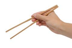 La mano derecha de la persona usando los palillos de bambú Fotos de archivo libres de regalías