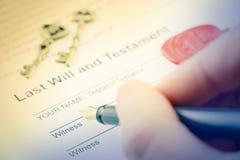 La mano derecha del hombre con la pluma que se prepara para firmar un impreso del último y testamento imagenes de archivo