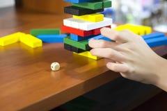 La mano desmonta la torre de barras de madera multicoloras imagen de archivo libre de regalías