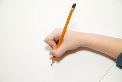 La mano destra del bambino che tiene una matita sopra sopra bianco Fotografia Stock Libera da Diritti