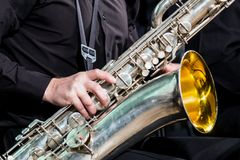 La mano destra del musicista in una camicia del nero riposa su un sassofono-baritono Primo piano Fotografia Stock