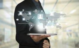 La mano di affari con le icone dell'applicazione la rete del globo e collega Fotografia Stock