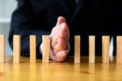 La mano di affari ferma il significato capovolto continuo di domino che ha ostacolato il fallimento Faccia tappa questo concetto  immagine stock