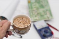La mano di cui sta tenendo il caffè su un fondo vago Immagine Stock Libera da Diritti