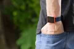 La mano di Man's in jeans intasca con l'orologio astuto sulla suoi natura del polso e fondo verde del bokeh degli alberi immagine stock