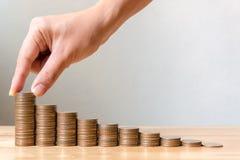 La mano di maschio o la femmina che mette le monete impila la crescita crescente s di punto Immagini Stock Libere da Diritti