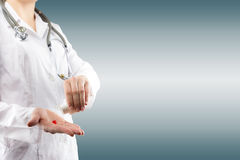 La mano di medico femminile che dà le pillole Chiuda sul colpo su grey vago Fotografia Stock