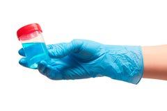La mano di medico femminile in guanto blu che tiene la raccolta di esemplare sterile di plastica trasparente contiene Fotografia Stock