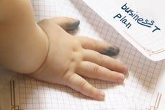 La mano di piccolo bambino è macchiata in inchiostro che si trova su pezzo di carta concetto di un principiante nell'affare Piano fotografia stock