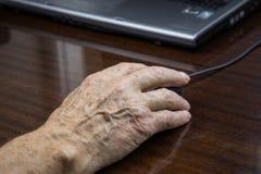 La mano di un uomo anziano usa un topo del computer immagini stock libere da diritti