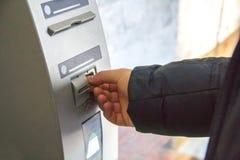 La mano di un uomo inserisce una carta di plastica nel recipiente della carta del cash machine immagini stock libere da diritti