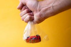 La mano di un uomo tiene una borsa trasparente di plastica in cui un'automobile rossa del giocattolo immagine stock