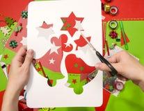 La mano di una donna che taglia un cartone bianco con il Natale modella , stelle e campane Fotografia Stock Libera da Diritti