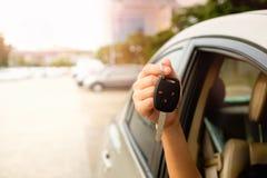 La mano di una donna che tiene una chiave dell'automobile Fotografia Stock