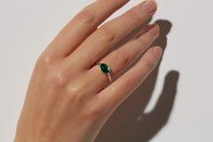 La mano di una donna con un anello verde fotografie stock