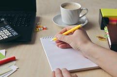 La mano di una donna sta tenendo una penna nera al primo piano dello scrittorio Studio ed e concetto di lavoro fotografia stock