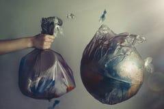 La mano di una donna tiene una borsa di immondizia accanto al globo di pianeta Terra Concetto di ecologia e di protezione dell'am fotografia stock