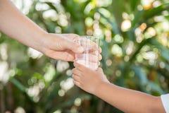 La mano di una donna tiene un vetro alla mano del ragazzo fotografia stock libera da diritti