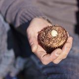 Bigné del cioccolato della tenuta della mano Fotografie Stock