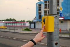 La mano di una ragazza con un orologio preme il bottone del passaggio pedonale Il bottone è acceso in pedone rosso e elettronico immagini stock