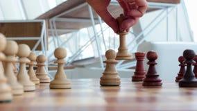 La mano di una ragazza fa un movimento con un pezzo degli scacchi sopra la scacchiera nella stanza Gioco degli scacchi, giochi da archivi video