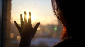 La mano di una ragazza inganna il vetro, provante a toccare il declino urbano e fermi che il ` s del sole rays, 4k, 3840x2160 video d archivio