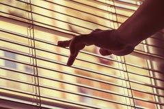 La mano di Woman's apre i ciechi e guarda attraverso la finestra fotografie stock