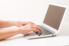 La mano di Womanche scrive sul computer portatile Fotografia Stock Libera da Diritti