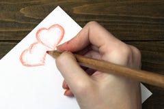La mano dibuja el lápiz de dos corazones Foto de archivo libre de regalías