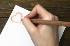 La mano dibuja un lápiz en el papel Fotos de archivo libres de regalías