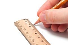 La mano dissipa una riga con una matita e un righello Fotografia Stock