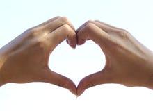 La mano due fa il cuore sul cielo Fotografie Stock