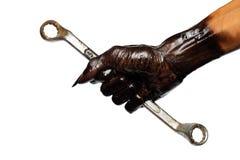 La mano e la chiave dell'uomo in olio per motori Immagini Stock Libere da Diritti