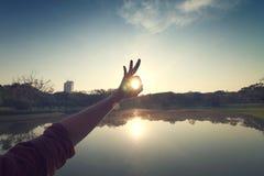 La mano ed il tramonto in parco Immagini Stock