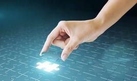La mano embute el pedazo que falta del rompecabezas en lugar Imagen de archivo