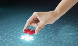 La mano embute el pedazo que falta del rompecabezas en lugar. Imágenes de archivo libres de regalías