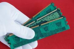 La mano en el guante blanco sostiene una tarjeta de la memoria de computadora tres Fotografía de archivo