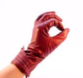La mano en el guante que muestra el gesto Imagen de archivo