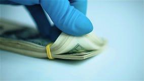 La mano en guante azul hojea a través de la pila de dólares de EE. UU. primer metrajes