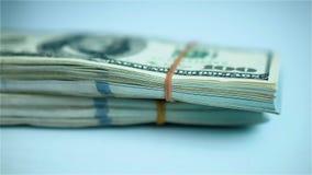 La mano en guante azul pone paquetes de paquetes del dólar de EE. UU. en la superficie blanca primer almacen de metraje de vídeo