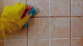La mano en guante protector amarillo lava la teja con espuma en fondo de la baldosa cerámica metrajes