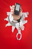 La mano en shakles sostiene el teléfono móvil Imagenes de archivo