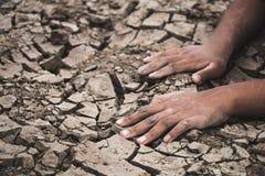 La mano en la tierra agrietó seco debido a la sequía imágenes de archivo libres de regalías