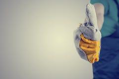 La mano en un guante protector que hace los pulgares sube la muestra Imagen de archivo libre de regalías