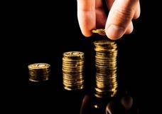 La mano entrega una pila de aumento de beneficios del gráfico de las monedas en fondo negro imágenes de archivo libres de regalías
